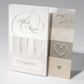 Hochzeitseinladung mit Eheringen und Herz im Sand